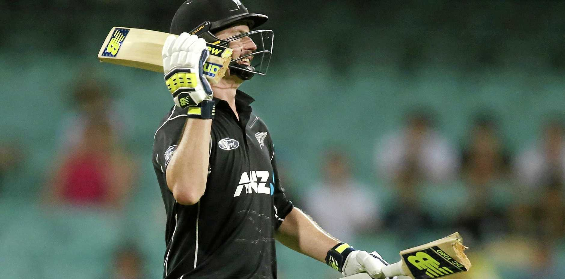 New Zealand's Colin Munro carries the two pieces of his bat after it broke while playing Australia