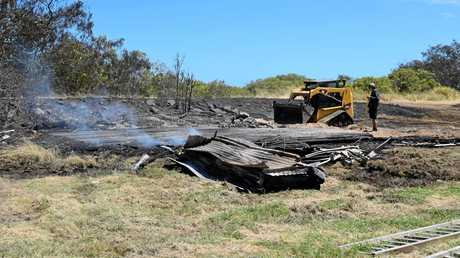 CLEANING UP: Workers remove the smouldering remains of the shed at Burnett Heads today.