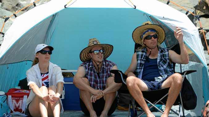 L-R Alyssa Shaw, Aaron Duckworth and Tony Patterson watch the beach volley ball at the Great Australian Beach Party in Yeppoon on Australia Day.