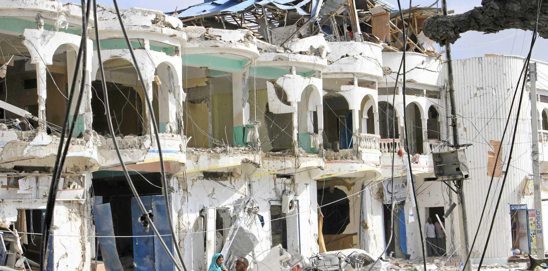 Somalis walk near a hotel heavily damaged by a car bomb blast in Mogadishu.