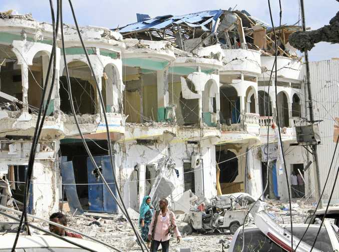 Somalis walk near a hotel heavily damaged by a car bomb blast in Mogadishu.