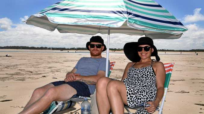 RELAXING DAY: Greg and Charlene Naumann sit at Elliott Heads Beach.