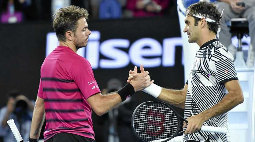 Roger Federer of Switzerland (right) shakes hands with compatriot Stan Wawrinka after winning their semi-final at the Australian Open.