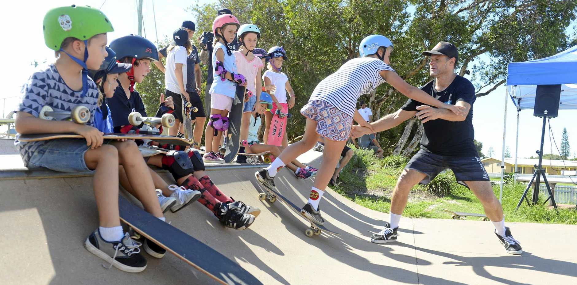 Ex-pro skater Trevor Ward teaches kids at Skate All Day at the Yamba Skate Park. INSET: Grant McGregor helps his daughter Dana learn to skate.