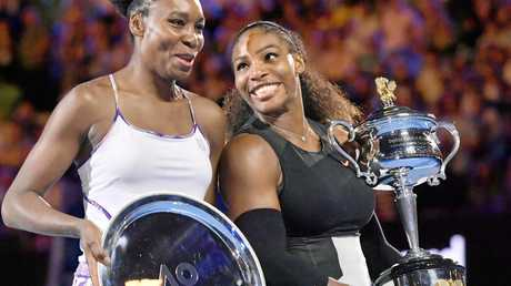 Serena Williams (R) and Venus Williams at the award ceremony following their Australian Open women's singles final in Melbourne