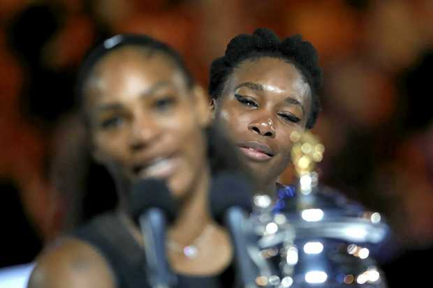 Venus Williams looks on as Serena Williams holds her trophy.