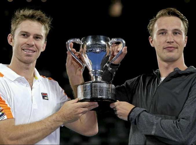 Australia's John Peers (left) and Finland's Henri Kontinen hold their trophy aloft after winning the men's doubles final against Bob and Mike Bryan of the US at the Australian Open.