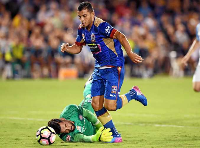 Andrew Nabbout of the Newcastle Jets gets past Melbourne City's Dean Bouzanis to score during their round 17 A-League match in Coffs Harbour.