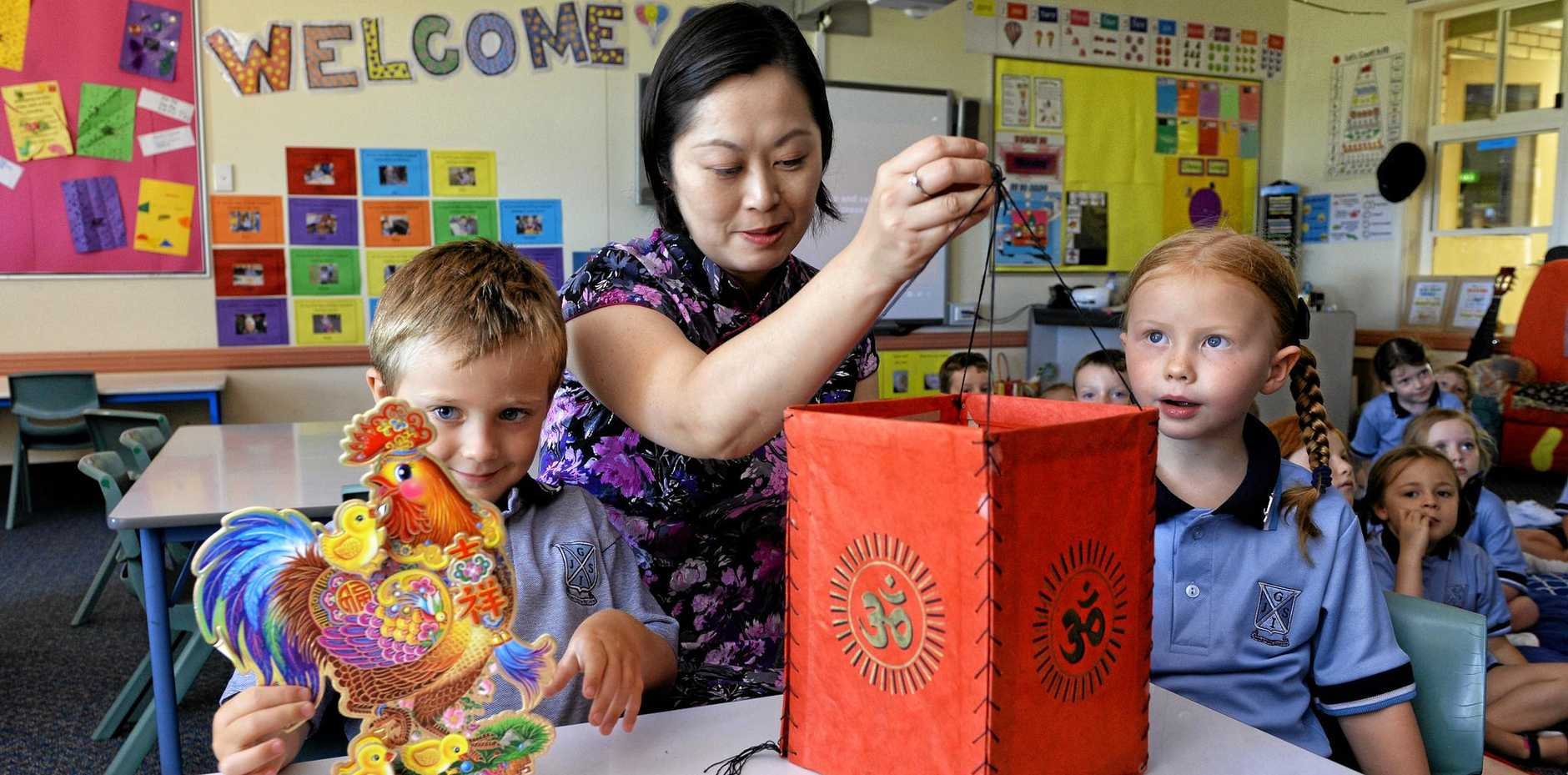 Mandarin teacher Alfany Takahashi shows Ipswich Junior Grammar School students Lucas Thompson and Grace Taylor some Chinese items during the lesson.