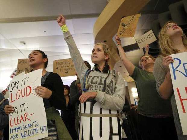 People opposed to President Donald Trump's executive order banning travel from seven Muslim-majority countries continue to demonstrate at Los Angeles International Airport Sunday, Jan. 29, 2017.