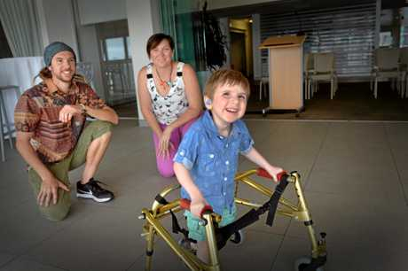 Cockayne Syndrome sufferer Felix Krupa, 3, with his parents Daniel and Pearl using a piece of equipment provided by The Board Meeting Surf Charity.