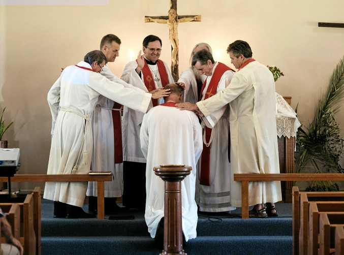 WELCOMED: Lutheran Bishop Paul Smith makes the sign of the cross over Pastor Mark Hampel during his installation service at Trinity Lutheran Church on a muggy Saturday afternoon.