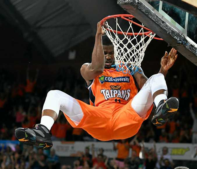 Tony Mitchell of the Taipans hangs from the rim after scoring during the round 17 NBL match between the Cairns Taipans and the Brisbane Bullets at Cairns Convention Centre