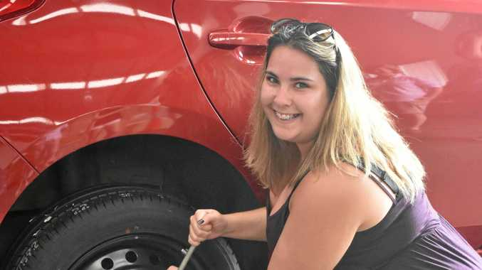 MISS FIX-IT: Toni Thomas learns how to change a tyre at the Black Toyota workshop.