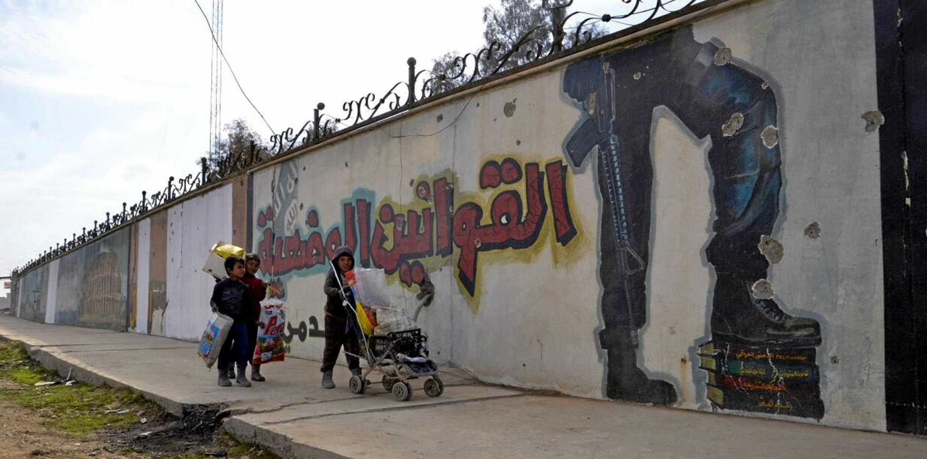 Iraqi boys from Mosul walk next to a mural contain graphics and slogans written by Islamic State that reads