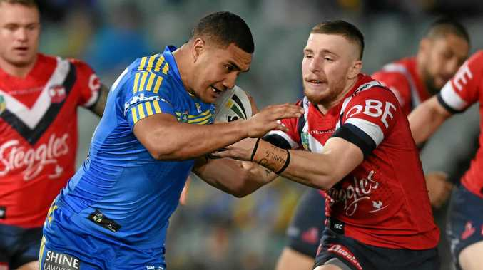 Peni Terepo (left) of the Eels pushes through a tackle by Jackson Hastings of the Roosters.