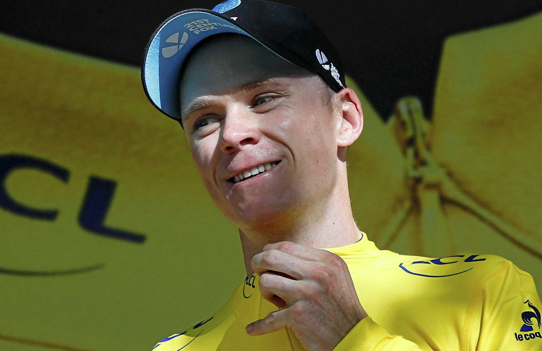 Britain's Chris Froome, wearing the overall leader's yellow jersey, celebrates on the podium after the 16th stage of the 2016 Tour de France.