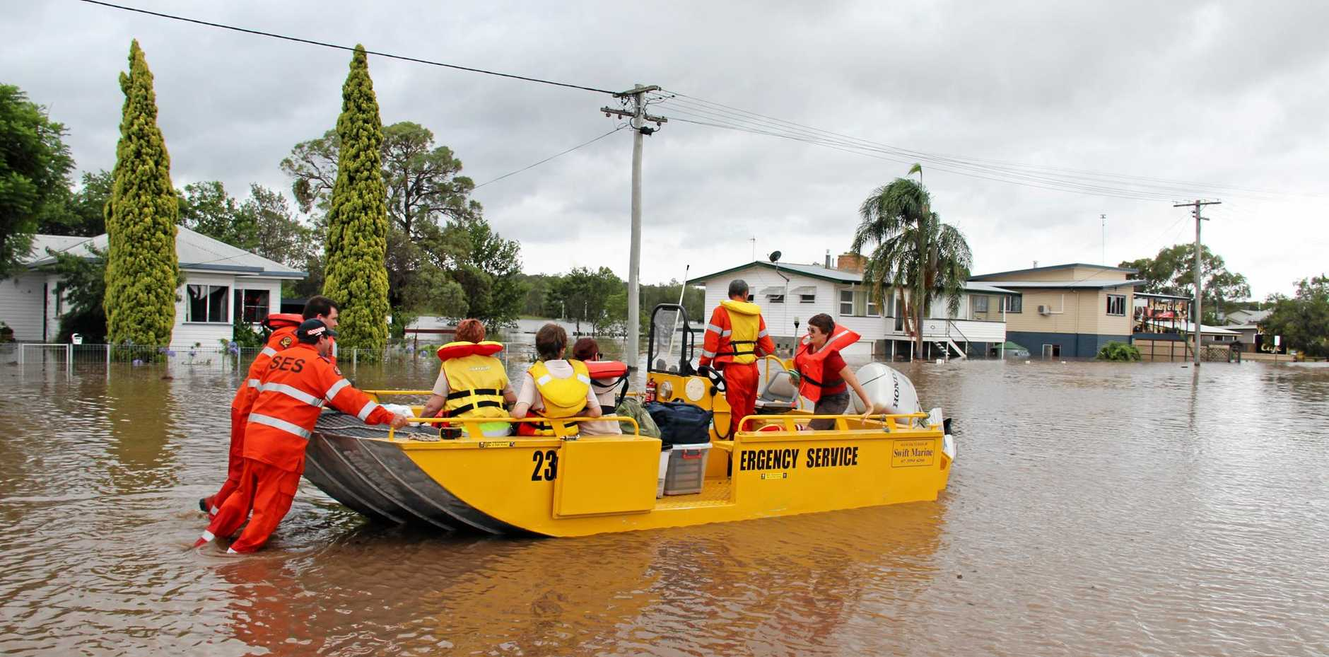 HARD WORK: Warwick SES volunteers in the floodwaters in Fitzroy St, transporting medical teams and supplies to affected areas in East Warwick in floods in 2013.