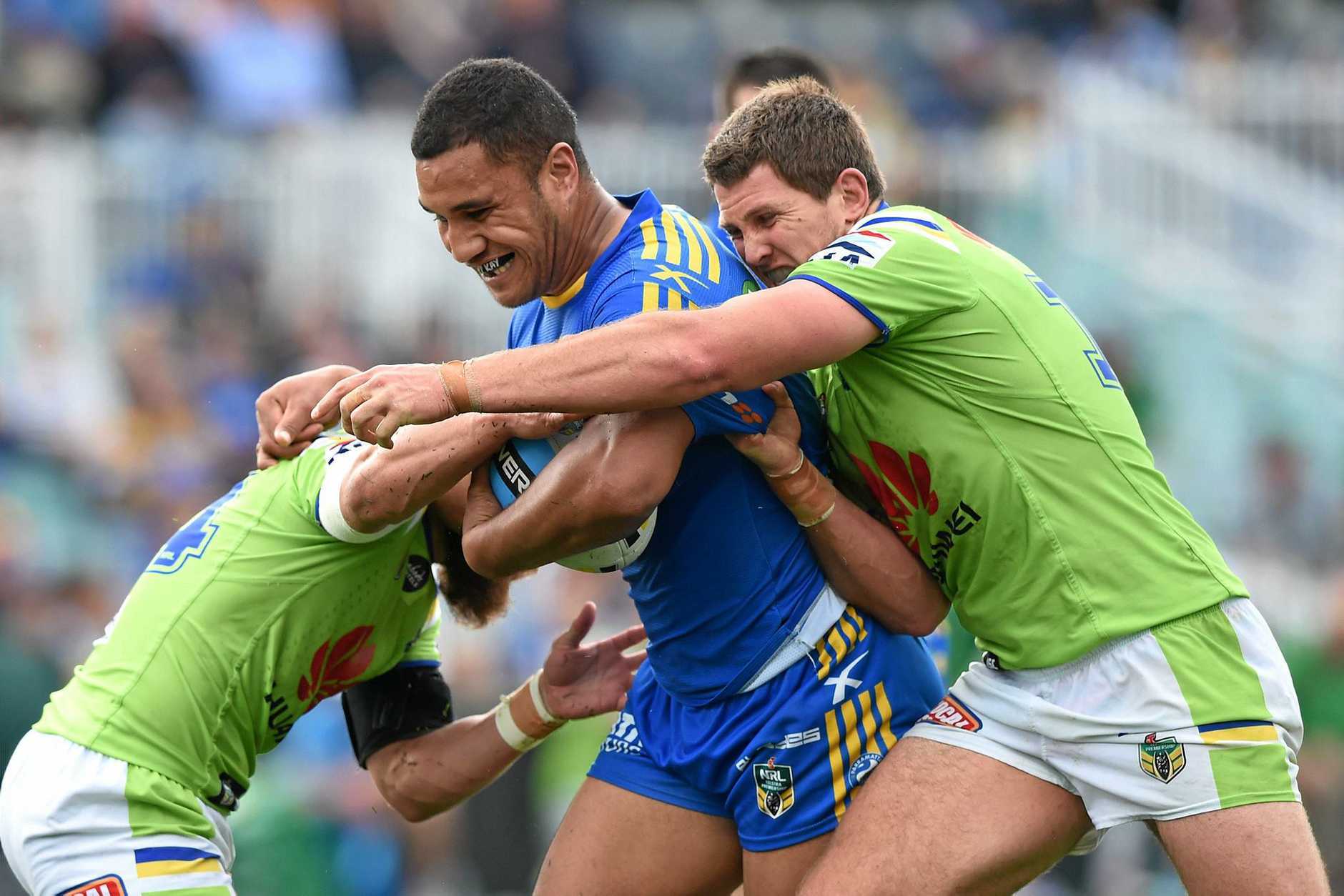Peni Terepo (centre) of the Eels is tackled by Jarrad Kennedy (right) and Kurt Baptiste of the Raiders.