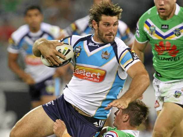The Gold Coast's David Taylor is brought down by Josh McCrone of the Raiders in 2014.