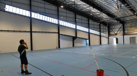 Cleaners get the massive indoor sports arena at Bundaberg's new $15 million Multiplex tidied up.
