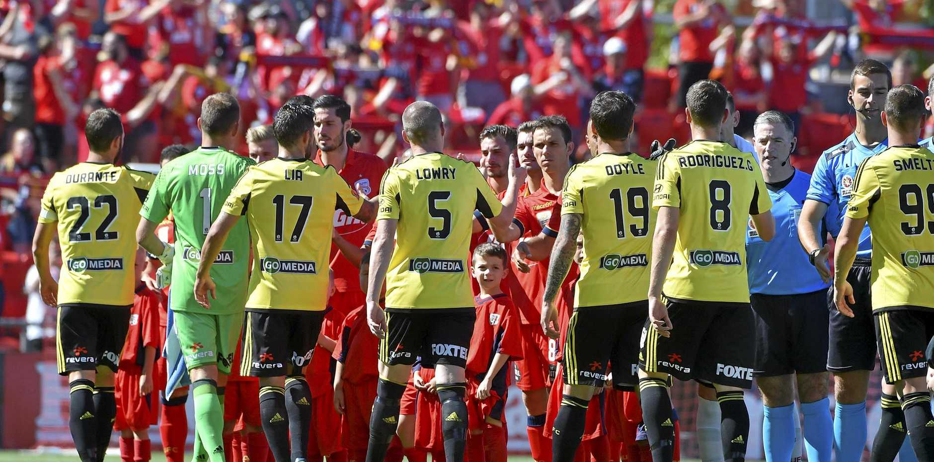 Adelaide United and Wellington Phoenix players line up before their round 17 A-League match at Coopers Stadium in Adelaide.