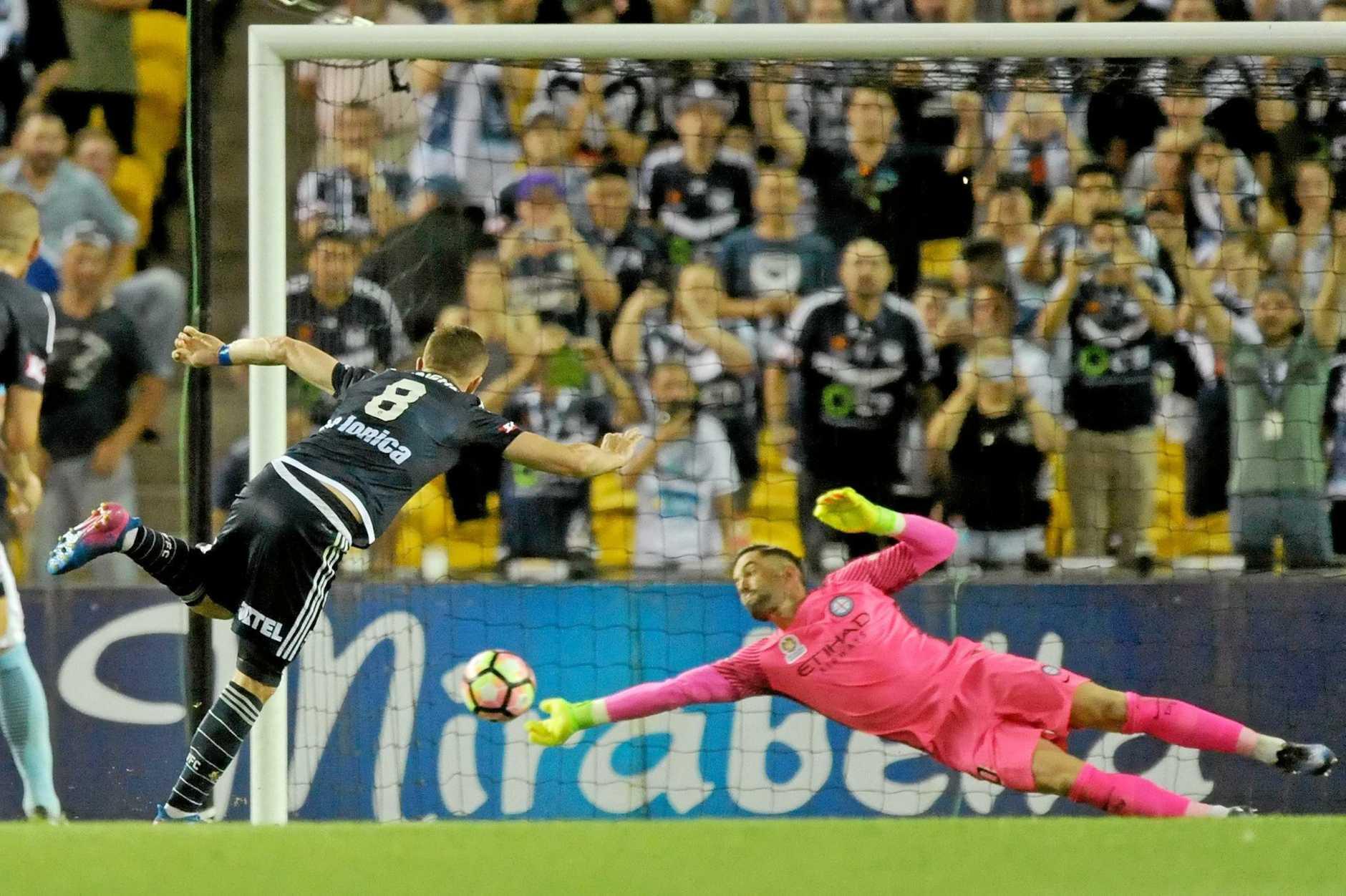 Melbourne City goalkeeper Dean Bouzanis dives to save Melbourne Victory striker Besart Berisha's penalty in Saturday night's heated derby at Etihad Stadium.