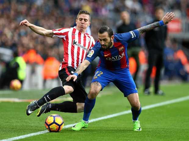 FC Barcelona midfielder Aleix Vidal (right) vies for the ball with Athletic Bilbao forward Iker Muniain.