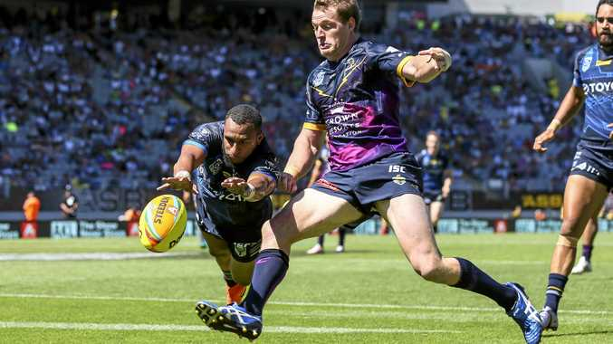 Gideon Gela-Mosby of the Cowboys scores despite the attentions of Tim Glasby of the Storm at the Auckland Nines.