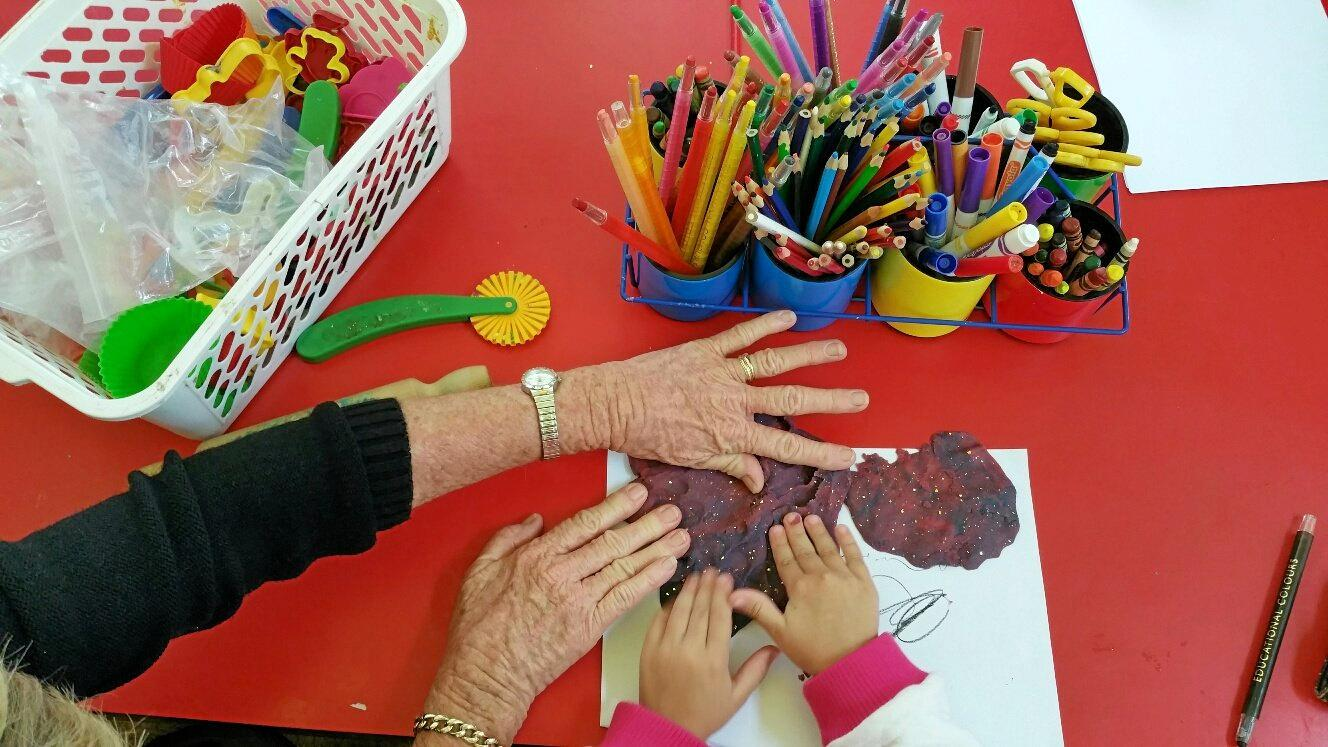 Caring hands of young and old at Mons playgroup centre.