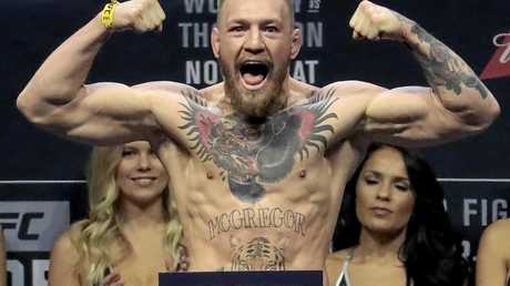 FILE - In this Friday, Nov. 11, 2016, file photo, Conor McGregor stands on a scale during the weigh-in event for his fight against Eddie Alvarez in UFC 205 mixed martial arts at Madison Square Garden in New York. Floyd Mayweather Jr. wants attention more than he wants a fight. And, really, let's be truthful here. It wouldn't be much of a fight if Mayweather and Conor McGregor met in a boxing ring. (AP Photo/Julio Cortez, File)