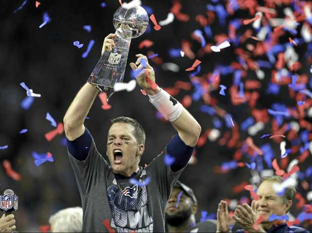 New England Patriots quarterback Tom Brady raises the Vince Lombardi Trophy after defeating the Atlanta Falcons in overtime at the NFL Super Bowl 51.