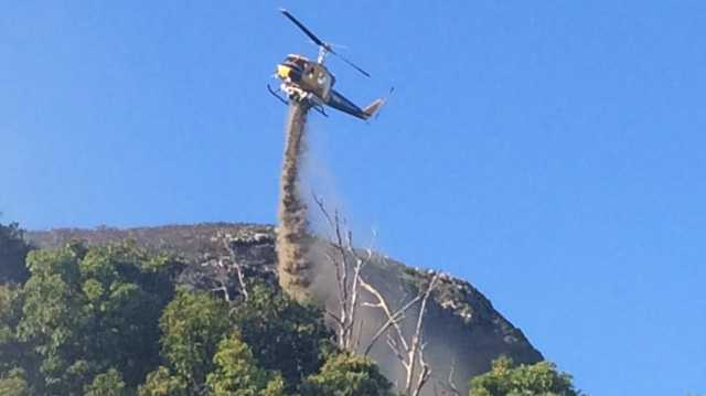 A waterbombing helicopter drops a load on a bushfire burning on the eastern side of Mt Coolum.