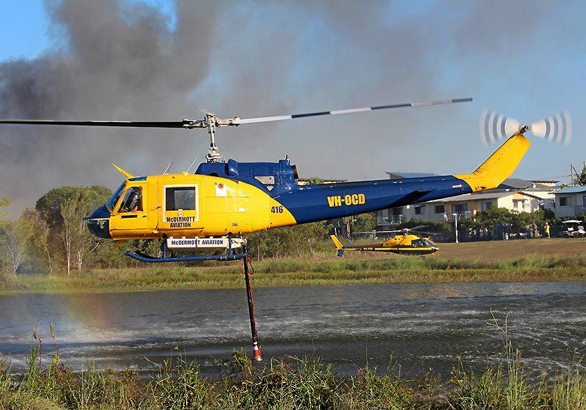 A WATER-BOMBING helicopter picks up water from a lake at the University of the Sunshine Coast to fight a bushfire at Sippy Downs. A new report warns to expect more frequent fire weather.