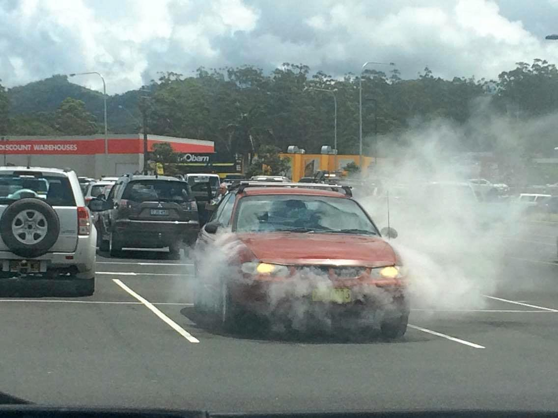 CAR FIRE: Firefighters extinguish a car on fire at Coffs Harbour Bunnings on Wednesday, February 8.