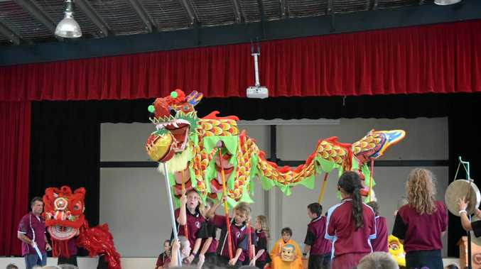 THRILL OF THE CHASE: Burnett Heads State School students, led by Alix Forrest (holding up the head) perform a dance with a Chinese dragon for Walkervale State School students. The dragon 'chases' a pearl carried by Lilly Matthews.