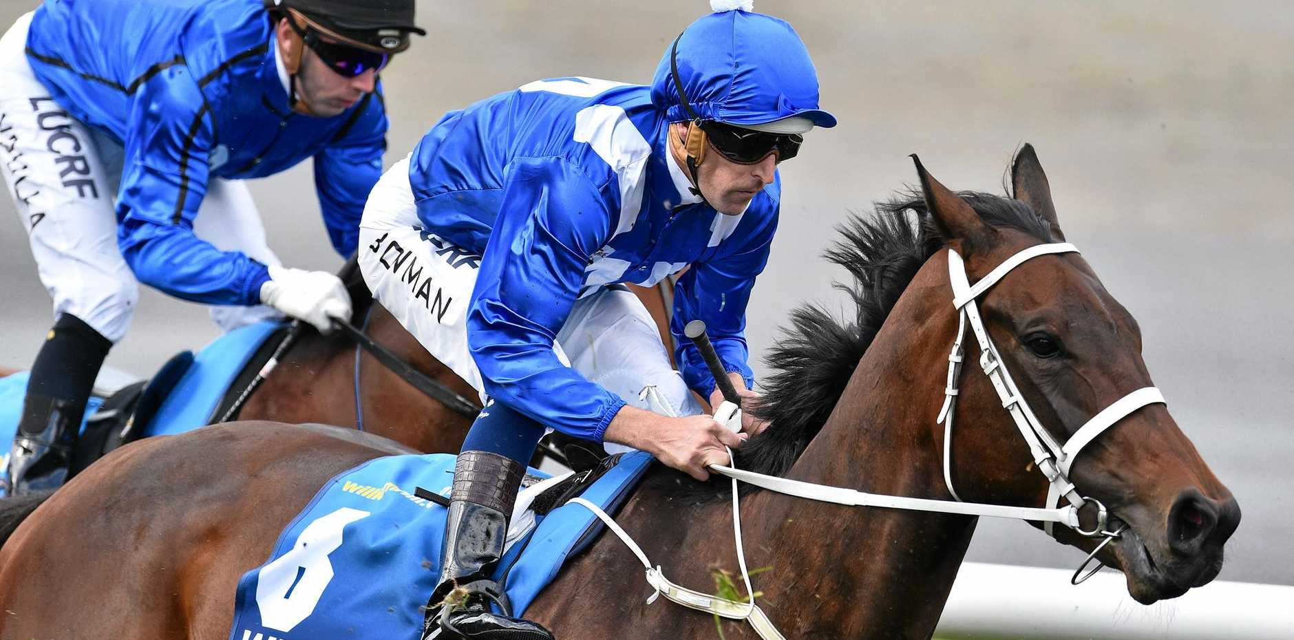Hugh Bowman rides Winx (right) past the post in the Cox Plate at Moonee Valley Racecourse last October.