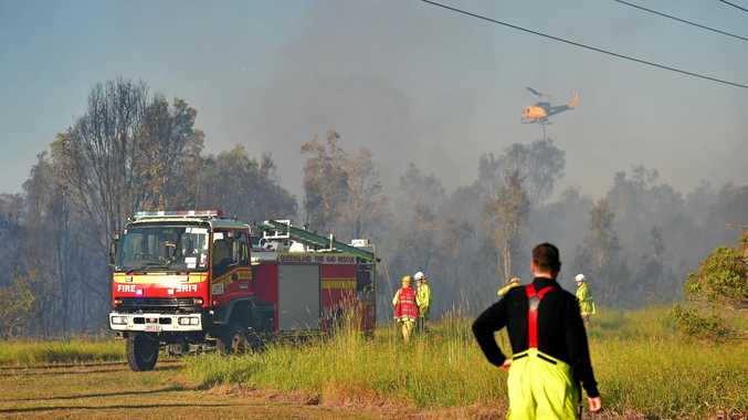 A waterbombing helicopter swoops over a bushfire that burnt on University of the Sunshine Coast land at Sippy Downs.