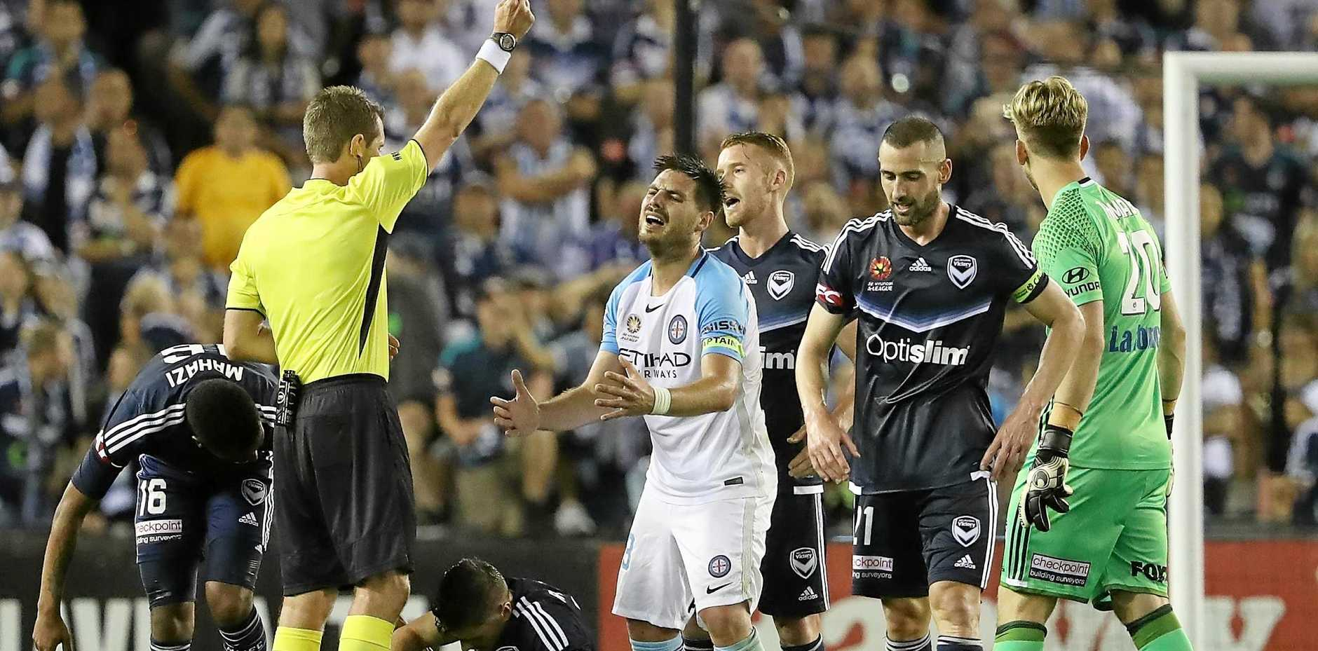 Bruno Fornaroli of Melbourne City is shown a yellow card by referee Chris Beath during the round 18 A-League match against the Melbourne Victory.