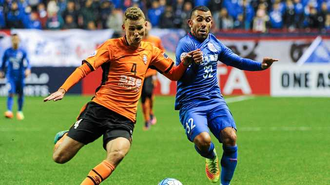 Argentine football player Carlos Tevez of China's Shanghai Shenhua (right) challenges Daniel Bowles of Australia's Brisbane Roar.