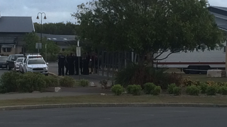 Police gathered at Unity College, Caloundra West as the hunt for a man who reports say could be armed, continues