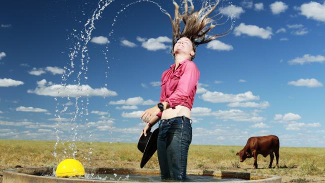 Jillaroo Taylah Armstrong cools off in the trough at Farm Paddock near Hughenden. Picture: Lachie Millard
