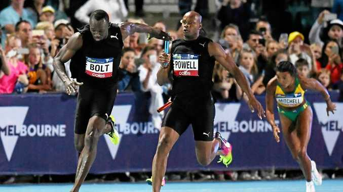 Jamaican sprinter Asafa Powell passes the baton to teammate Usain Bolt in the mixed 4x100 relay.