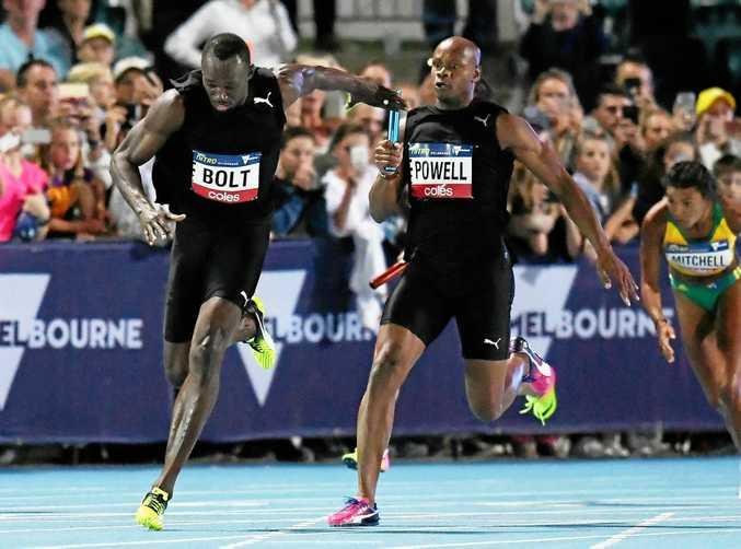 Jamaican sprinter Asafa Powell passes the baton to teammate Usain Bolt in the mixed 4x100 relay.