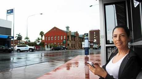 Marcela Posada wiating for a bus in the rain.