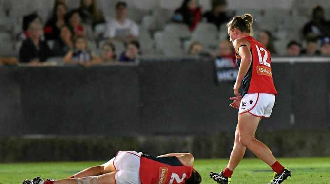 Meg Downie of Melbourne on the ground after being knocked out as Shelly Scott comes in to check on her.