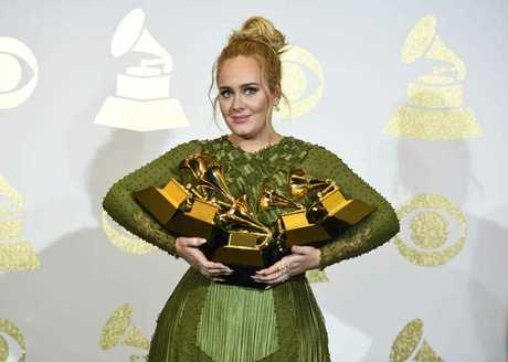 Adele poses in the press room with the awards for album of the year for