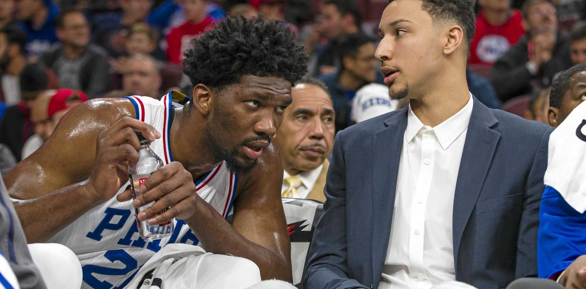 Philadelphia 76ers centre Joel Embiid (left) listens to injured Australian teammate Ben Simmons on the bench during the first half of an NBA basketball game against the Toronto Raptors.