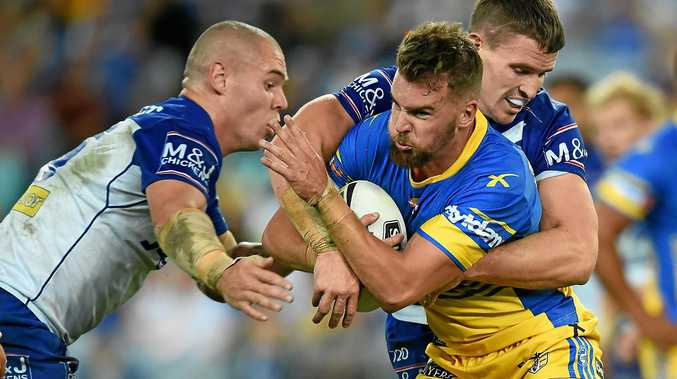 Clint Gutherson of the Eels is tackled by David Klemmer (left) and Tim Browne of the Bulldogs.