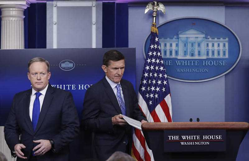 Former National Security Adviser Michael Flynn walks past White House press secretary Sean Spicer to the podium to speak during the daily news briefing at the White House. FILE PHOTO